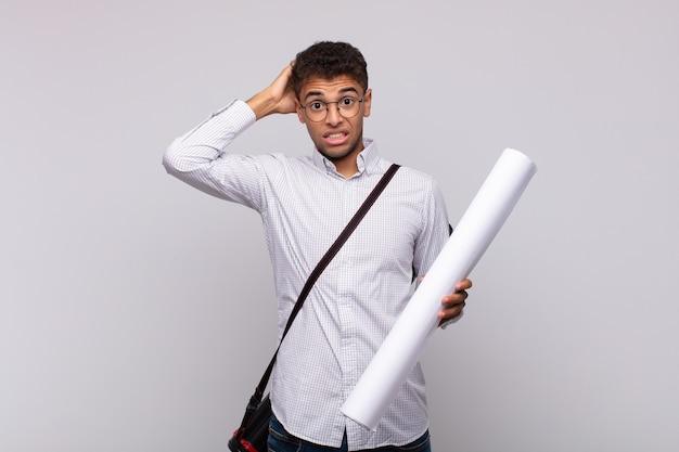 Jonge architect die zich gestrest, bezorgd, angstig of bang voelt, met de handen op het hoofd, in paniek raakt bij vergissing