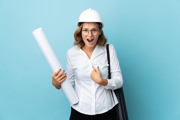 Jonge architect georgische vrouw met helm en blauwdrukken bedrijf over geïsoleerde achtergrond met verrassingsgelaatsuitdrukking