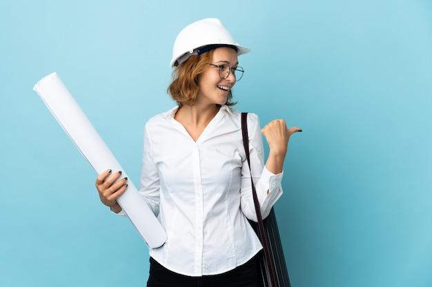 Jonge architect georgische vrouw met helm en blauwdrukken bedrijf over geïsoleerde achtergrond wijst naar de zijkant om een product te presenteren