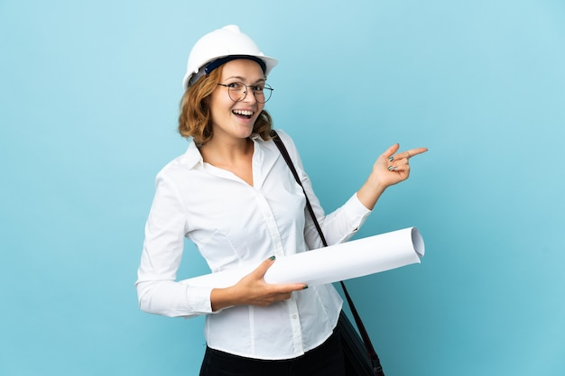 Jonge architect georgische vrouw met helm en blauwdrukken bedrijf over geïsoleerde achtergrond wijzende vinger naar de zijkant