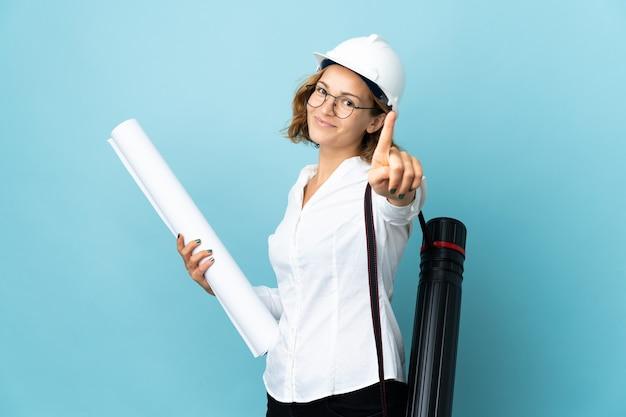 Jonge architect georgische vrouw met helm en blauwdrukken houden over geïsoleerde achtergrond die en een vinger opheft