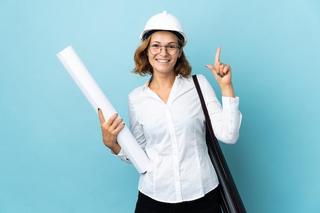 Jonge architect georgische vrouw met helm en blauwdrukken houden over geïsoleerde die een geweldig idee benadrukken