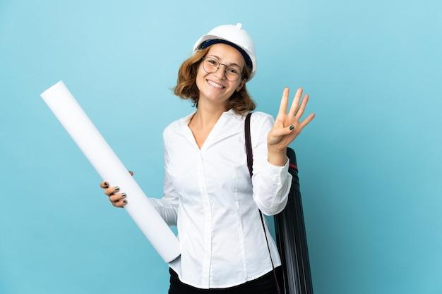 Jonge architect georgische vrouw met helm en blauwdrukken houden over geïsoleerde muur gelukkig en vier tellen met vingers