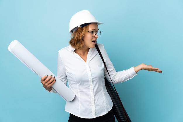 Jonge architect georgische vrouw met helm en blauwdrukken houden over geïsoleerde muur met verrassingsuitdrukking terwijl zij kant kijkt