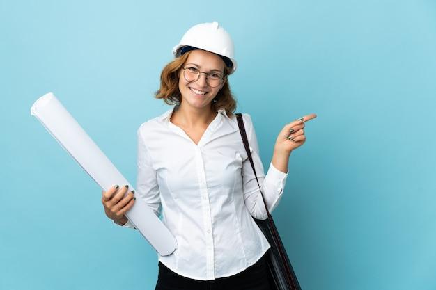 Jonge architect georgische vrouw met helm en geïsoleerdet blauwdrukken