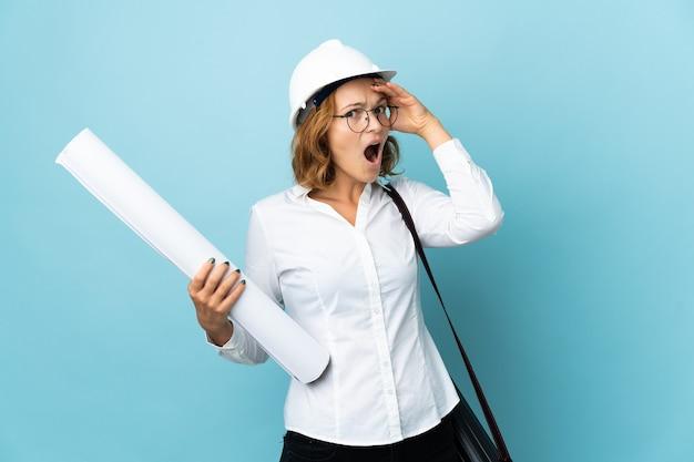 Jonge architect georgische vrouw met helm en met blauwdrukken over geïsoleerde achtergrond en doet een verrassingsgebaar terwijl ze naar de zijkant kijkt