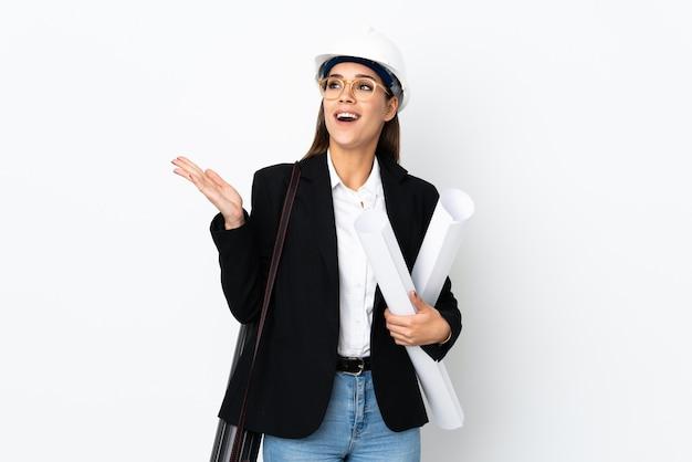 Jonge architect kaukasische vrouw met helm en blauwdrukken te houden