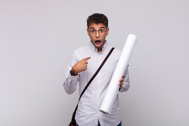 Jonge architect-man die zich blij, verrast en trots voelt en naar zichzelf wijst met een opgewonden, verbaasde blik