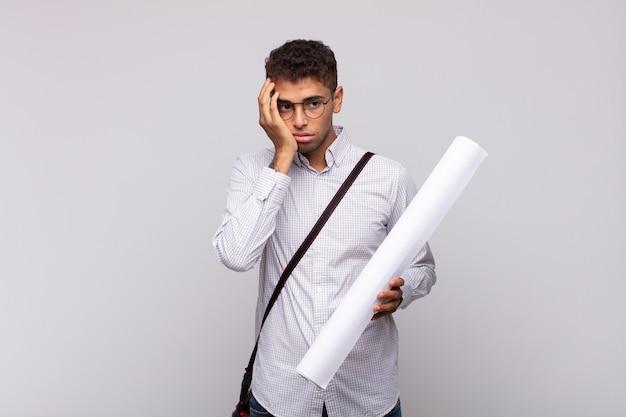 Jonge architect-man die zich verveeld, gefrustreerd en slaperig voelt na een vermoeiende, saaie en vervelende taak, gezicht met hand vasthoudend