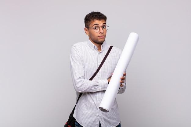 Jonge architect-man haalt zijn schouders op, voelt zich verward en onzeker, twijfelt met gekruiste armen en kijkt verbaasd