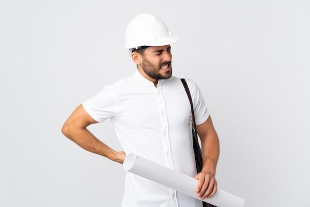 Jonge architect man met helm en blauwdrukken geïsoleerd op een witte achtergrond te houden die lijden aan rugpijn omdat ze zich hebben ingespannen
