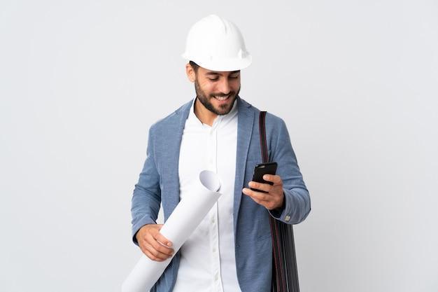 Jonge architect man met helm en blauwdrukken geïsoleerd op een witte achtergrond te houden, een bericht verzenden met de mobiele telefoon