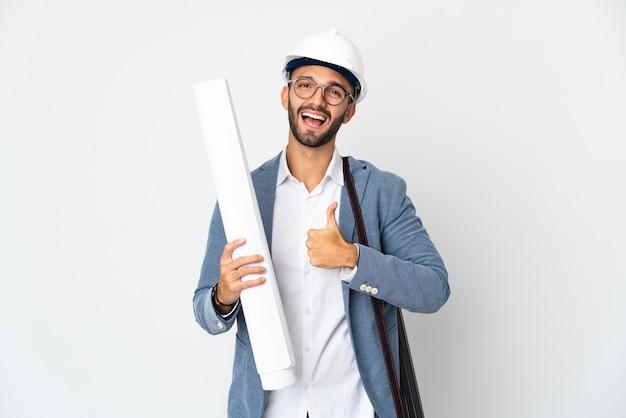 Jonge architect man met helm en blauwdrukken geïsoleerd op een witte achtergrond te houden met een duim omhoog gebaar