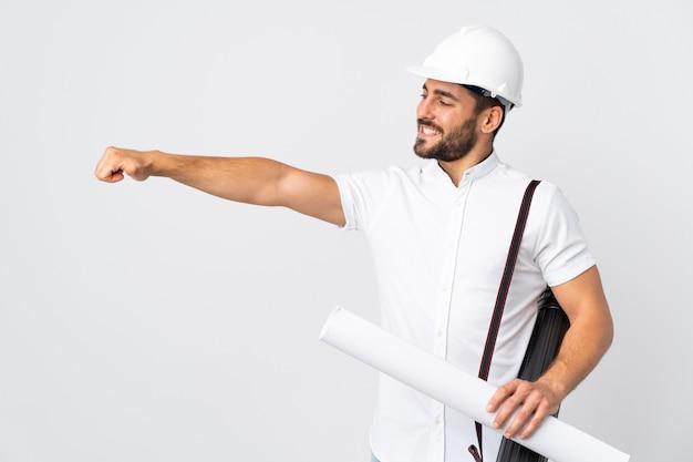 Jonge architect man met helm en blauwdrukken geïsoleerd op een witte muur te houden met een duim omhoog gebaar