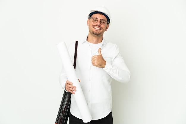 Jonge architect man met helm en blauwdrukken geïsoleerd op wit te houden met een duim omhoog gebaar