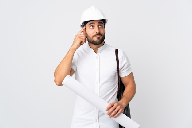 Jonge architect man met helm en blauwdrukken geïsoleerd op wit te houden met twijfels en denken