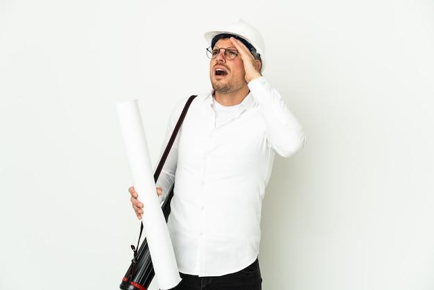 Jonge architect man met helm en blauwdrukken geïsoleerd op wit te houden terwijl hij naar de zijkant kijkt