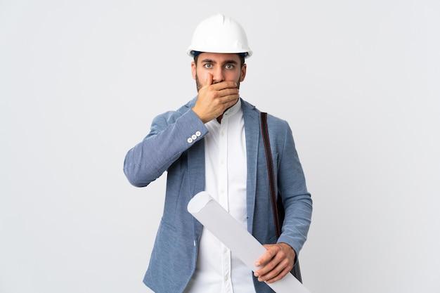 Jonge architect man met helm en blauwdrukken geïsoleerd op wit te houden voor mond met hand