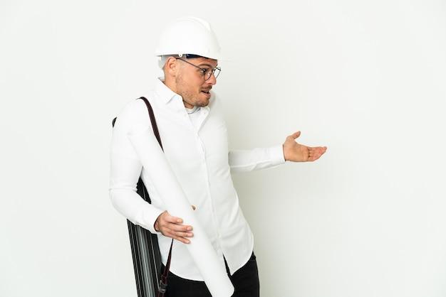 Jonge architect man met helm en blauwdrukken geïsoleerd te houden