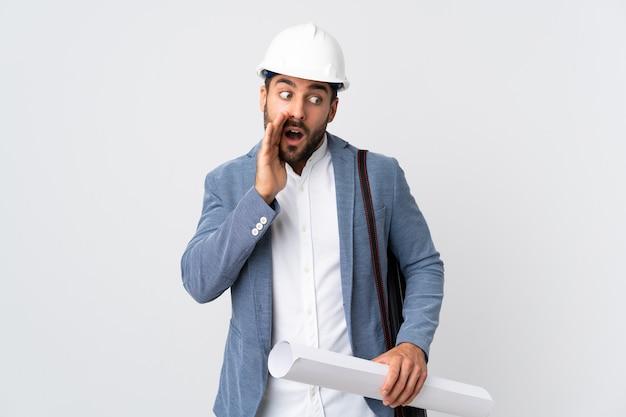 Jonge architect man met helm en blauwdrukken houden geïsoleerd op een witte muur iets met verrassingsgebaar fluisteren terwijl naar de zijkant kijken