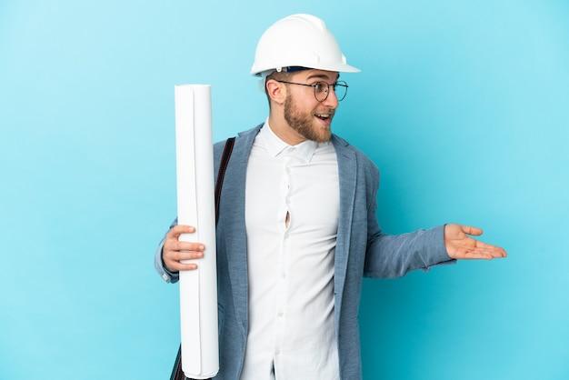 Jonge architect man met helm en blauwdrukken houden over geïsoleerde achtergrond met verrassing expressie terwijl op zoek naar kant
