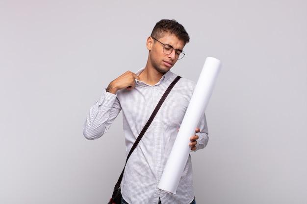 Jonge architect-man voelt zich gestrest, angstig, moe en gefrustreerd, trekt de nek van het shirt, kijkt gefrustreerd door het probleem