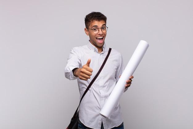 Jonge architect-man voelt zich trots, zorgeloos, zelfverzekerd en gelukkig, positief glimlachend met duimen omhoog