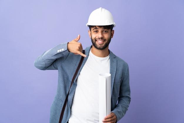 Jonge architect marokkaanse man met helm en blauwdrukken houden over geïsoleerd telefoongebaar maken