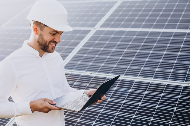 Jonge architect staat bij zonnepanelen en maakt diagnostiek op de computer