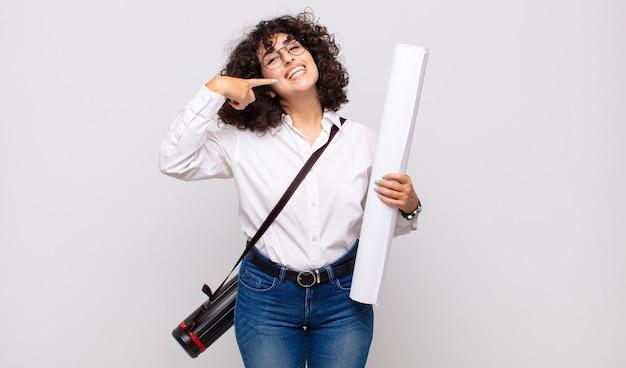 Jonge architect vrouw glimlachend vol vertrouwen wijzend naar eigen brede glimlach, positieve, ontspannen, tevreden houding