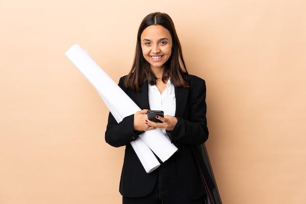 Jonge architect vrouw met blauwdrukken over geïsoleerde achtergrond een bericht verzenden met de mobiele telefoon