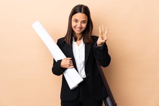Jonge architect vrouw met blauwdrukken over geïsoleerde achtergrond gelukkig en drie tellen met vingers