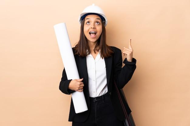 Jonge architect vrouw met blauwdrukken over geïsoleerde benadrukt en verrast