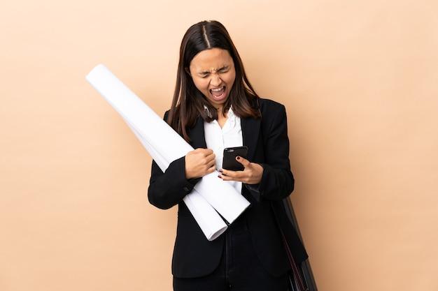 Jonge architect vrouw met blauwdrukken over geïsoleerde muur met telefoon in overwinning positie