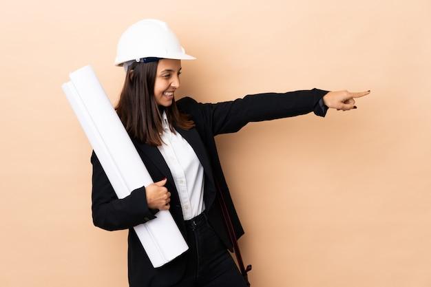 Jonge architect vrouw met blauwdrukken over geïsoleerde wijzende vinger aan de zijkant en het presenteren van een product