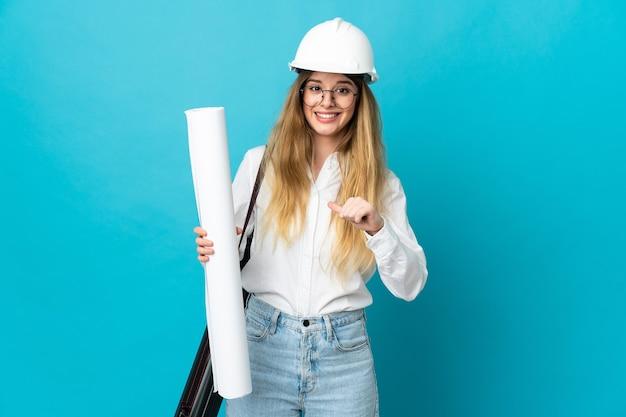 Jonge architect vrouw met helm en blauwdrukken bedrijf geïsoleerd op blauwe achtergrond met verrassing gelaatsuitdrukking