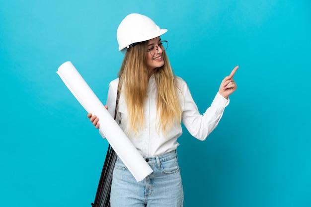Jonge architect vrouw met helm en blauwdrukken geïsoleerd op blauwe achtergrond te houden wijzende vinger naar de zijkant