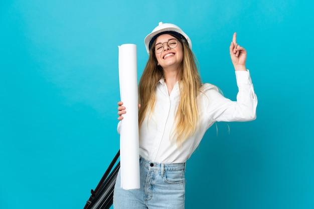 Jonge architect vrouw met helm en blauwdrukken geïsoleerd op blauwe muur te houden die een geweldig idee benadrukt