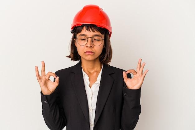 Jonge architect vrouw met rode helm geïsoleerd op een witte achtergrond ontspant na een zware werkdag, ze voert yoga uit.