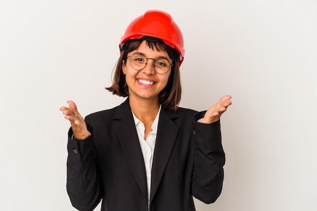 Jonge architect vrouw met rode helm geïsoleerd op een witte achtergrond voelt zich zelfverzekerd en geeft een knuffel aan de camera.