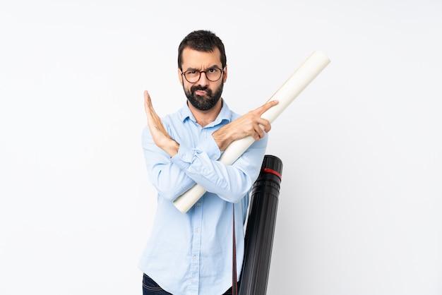 Jonge architectenmens die met baard over geïsoleerde witte muur geen gebaar maken