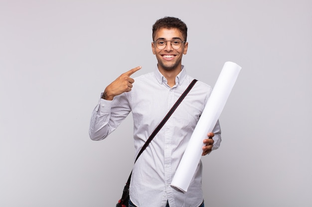 Jonge architectenmens die zelfverzekerd glimlacht wijzend naar eigen brede glimlach, positieve, ontspannen, tevreden houding
