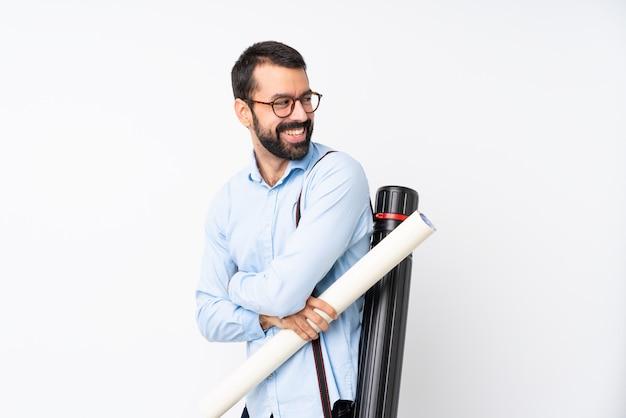 Jonge architectenmens met baard over geïsoleerd wit met gekruiste en gelukkige wapens