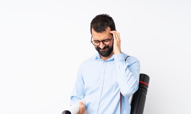 Jonge architectenmens met baard over geïsoleerd wit met hoofdpijn