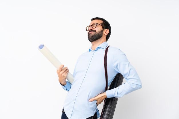 Jonge architectenmens met baard over geïsoleerde witte muur die aan rugpijn lijden omdat hij zich heeft ingespannen