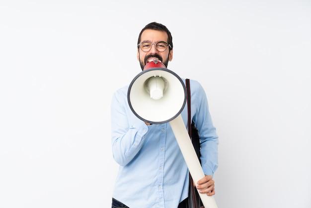 Jonge architectenmens met baard over geïsoleerde witte muur die door een megafoon schreeuwt