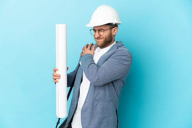 Jonge architectenmens met helm die en blauwdrukken over geïsoleerd houdt die aan pijn in schouder lijden omdat hij zich heeft ingespannen