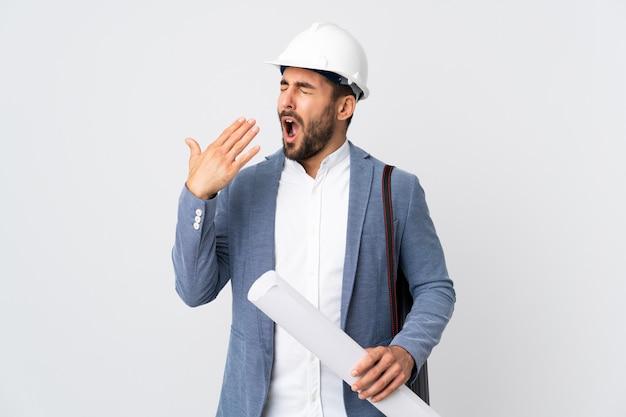 Jonge architectenmens met helm en blauwdrukken houden die op witte muur geeuwen en wijd open mond behandelen met hand