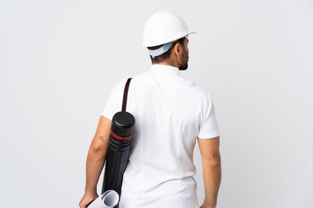 Jonge architectenmens met helm en blauwdrukken houden die op witte muur in achterpositie wordt geïsoleerd en kant die kijkt