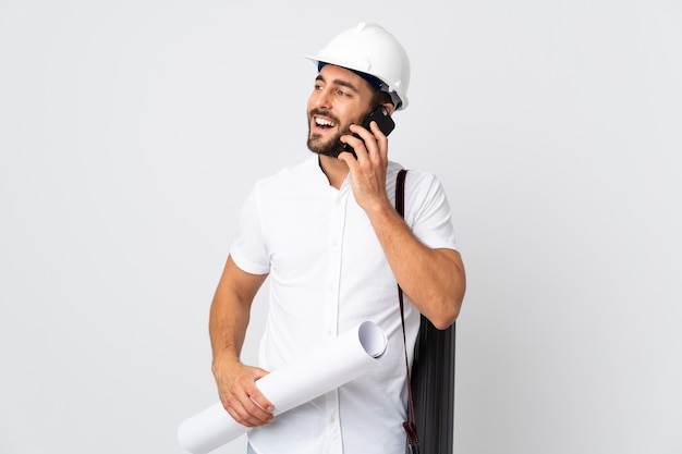 Jonge architectenmens met helm en blauwdrukken houden die op witte muur worden geïsoleerd die een gesprek met de mobiele telefoon houden